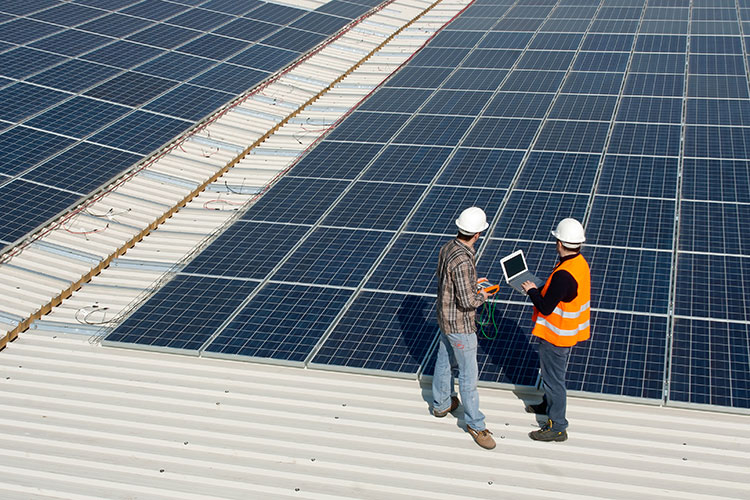 roof with solar panels and workers